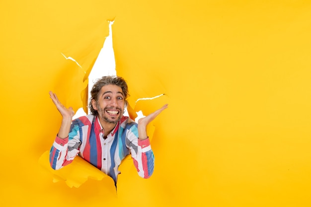 Szczęśliwy i emocjonalny młody facet pozuje do kamery przez rozdartą dziurę w żółtym papierze
