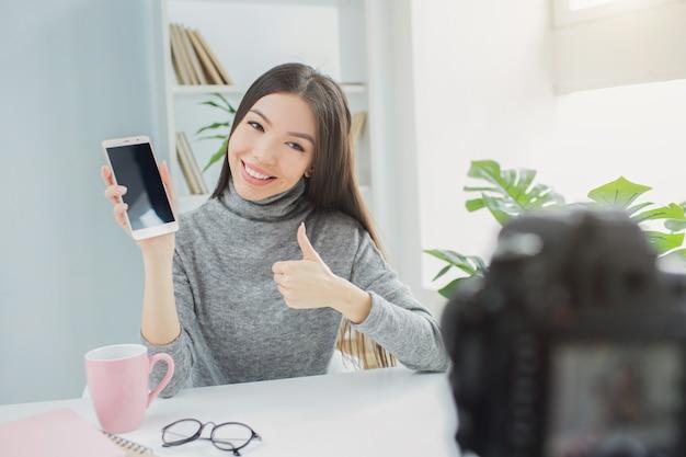 Szczęśliwy i fajny bloger pokazuje telefon do kamery vlogowej