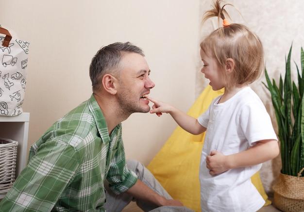 Szczęśliwy i kochający ojciec bawi się w domu ze swoją małą córeczką