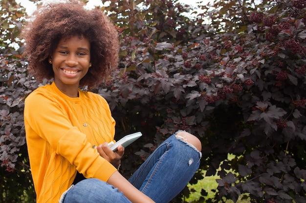 Szczęśliwy i młody uczeń afroamerykanów w parku