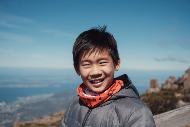 Szczęśliwy i pewny siebie rasy mieszanej rasy azjatyckiej chłopiec uśmiecha się nad widokiem na góry