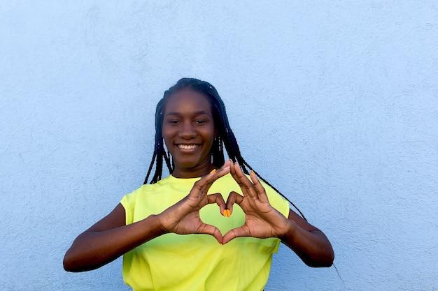 Szczęśliwy i piękny afroamerykanin pokazuje serce rękami