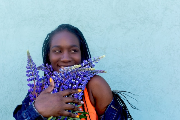 Szczęśliwy i piękny afroamerykanin z fioletowymi kwiatami
