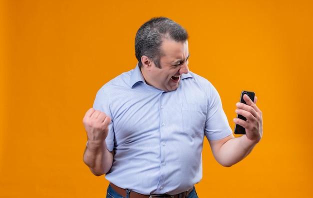 Szczęśliwy i podekscytowany mężczyzna w średnim wieku w niebieskiej koszuli w paski, trzymając telefon komórkowy i unosząc zaciśniętą pięść po zwycięstwie stojąc