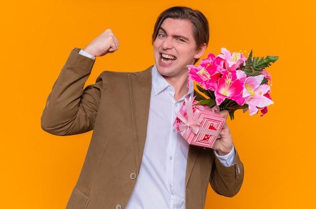 Szczęśliwy i podekscytowany młody mężczyzna trzyma prezent i bukiet kwiatów zaciskając pięść, gratulując międzynarodowego dnia kobiet stojącego nad pomarańczową ścianą