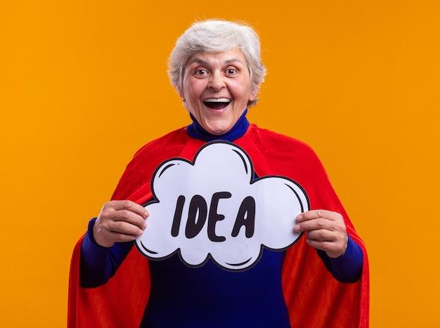 Szczęśliwy i podekscytowany starszy superbohater kobieta ubrany w czerwoną pelerynę, trzymając znak dymek z pomysłem na słowo, patrząc na kamery uśmiechający się radośnie stojąc na pomarańczowym tle