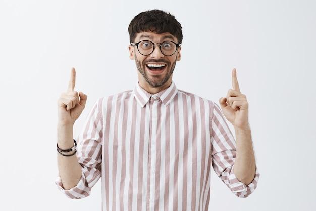 Szczęśliwy i podekscytowany stylowy brodaty facet pozuje przy białej ścianie w okularach