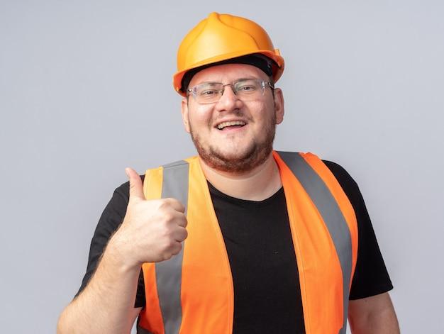 Szczęśliwy i pozytywny budowniczy mężczyzna w kamizelce budowlanej i kasku ochronnym, patrzący na kamerę, uśmiechający się radośnie pokazując kciuk do góry stojący nad białymi