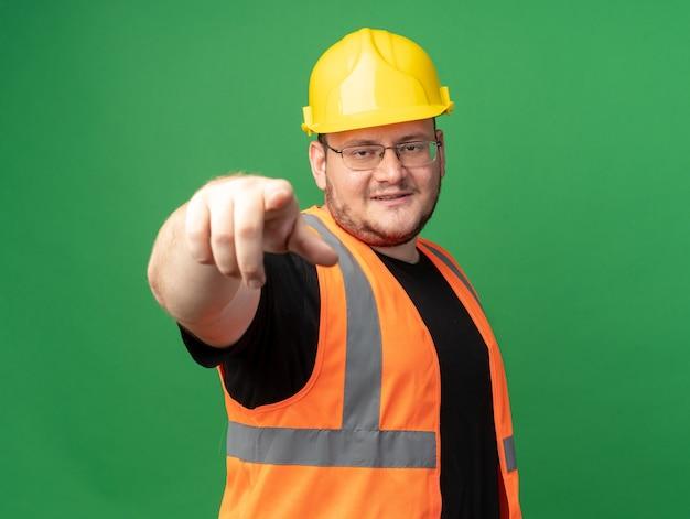 Szczęśliwy i pozytywny człowiek budowniczy w kamizelce budowlanej i wskazującym kasku ochronnym