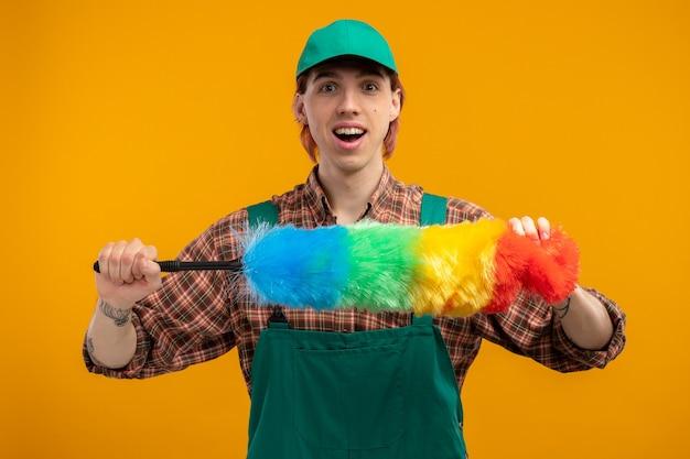 Szczęśliwy i pozytywny młody człowiek sprzątający w kombinezonie w kratę i czapce, trzymający kolorową miotełkę, uśmiechający się wesoło