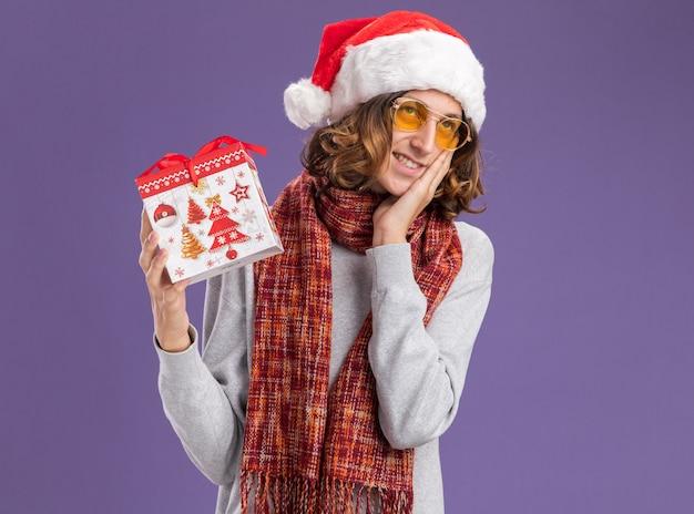 Szczęśliwy i pozytywny młody człowiek ubrany w świąteczny kapelusz mikołaja i żółte okulary z ciepłym szalikiem na szyi trzymający prezent świąteczny patrzący w górę uśmiechnięty radośnie stojący nad fioletową ścianą