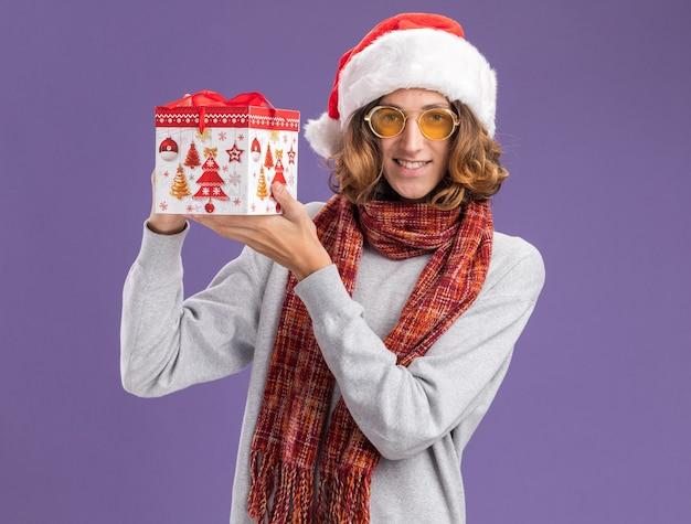 Szczęśliwy i pozytywny młody człowiek w świątecznej czapce mikołaja i żółtych okularach z ciepłym szalikiem na szyi trzyma prezent świąteczny patrząc w kamerę uśmiechnięty wesoło stojąc na fioletowym tle