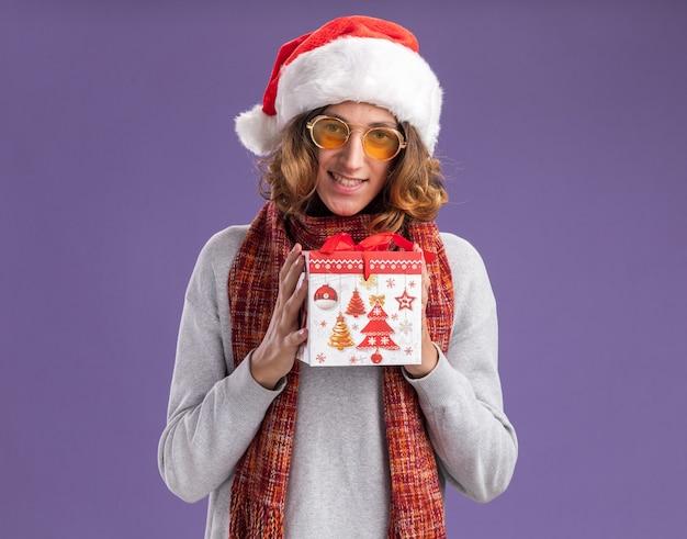 Szczęśliwy i pozytywny młody człowiek w świątecznym czapce mikołaja i żółtych okularach z ciepłym szalikiem na szyi trzymający prezent świąteczny patrząc na kamerę z uśmiechem na twarzy stojącej na fioletowym tle