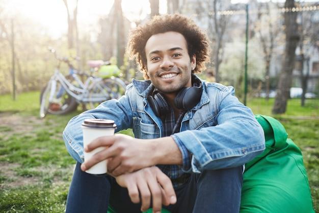 Szczęśliwy i pozytywny młody uczeń z fryzurą afro w modnych ubraniach siedzi w parku, uśmiechając się szeroko i pijąc kawę.