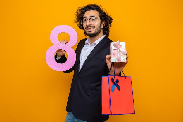 Szczęśliwy i pozytywny przystojny mężczyzna w garniturze, trzymając obecną papierową torbę z prezentem i numerem osiem, uśmiechnięty pewny siebie, świętujący międzynarodowy dzień kobiet 8 marca
