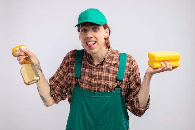 Szczęśliwy i radosny młody człowiek sprzątający w kombinezonie w kratę i czapce, trzymając gąbkę i spray do czyszczenia, patrząc uśmiechnięty radośnie wystający język