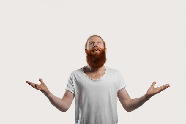 Szczęśliwy i uśmiechnięty mężczyzna w białej koszulce wygrywa nagrodę i otwiera ramiona