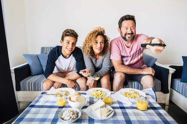 Szczęśliwy i wesoły kaukaski rodzina razem obiad w domu. biała ściana i jasny obraz. razem ciesz się dniem uśmiechając się i patrząc z miłością i przyjaźnią. patrząc w telewizji