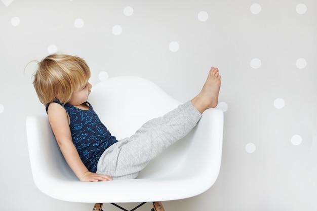 Szczęśliwy i zabawny śliczny dwuletni chłopiec ubrany w piżamę siedzi na białym krześle, unosząc nogi i pozując. koncepcja dzieci i szczęścia.