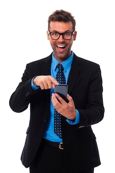 Szczęśliwy i zdziwiony biznesmen, wskazując na telefon komórkowy