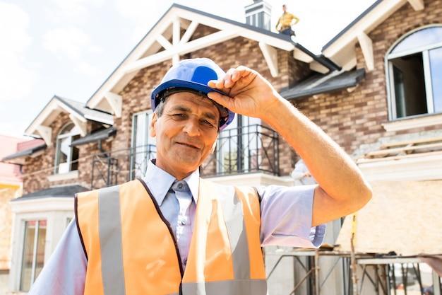Szczęśliwy indyjski architekt architekt na placu budowy patrzący na kamerę pewny siebie kierownik budowy w niebieskim kasku i żółtej kamizelce bezpieczeństwa portret udanego dojrzałego inżyniera budownictwa civil