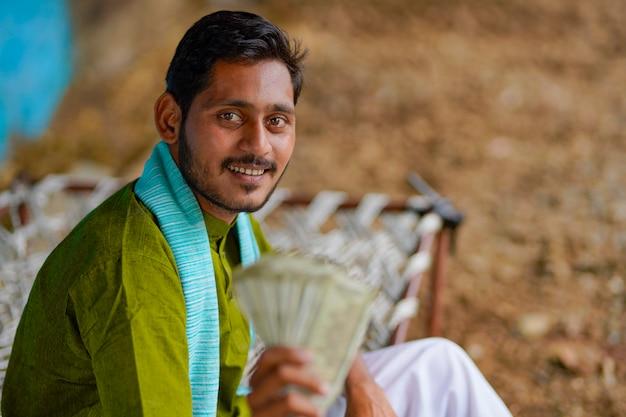 Szczęśliwy indyjski rolnik pokazując pieniądze w domu.