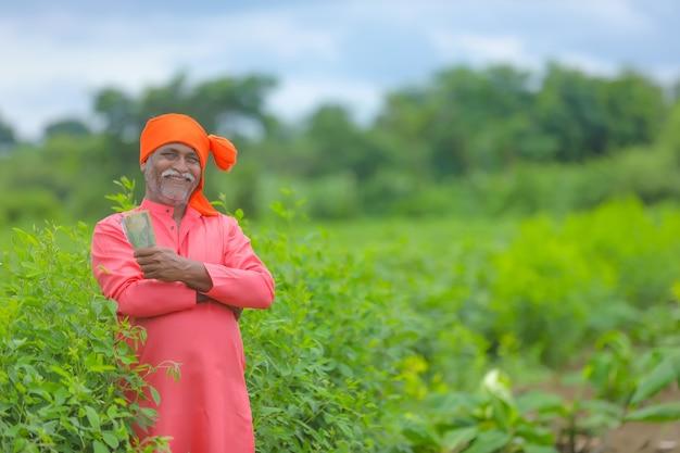 Szczęśliwy indyjski rolnik pokazujący rupie indyjskie w polu