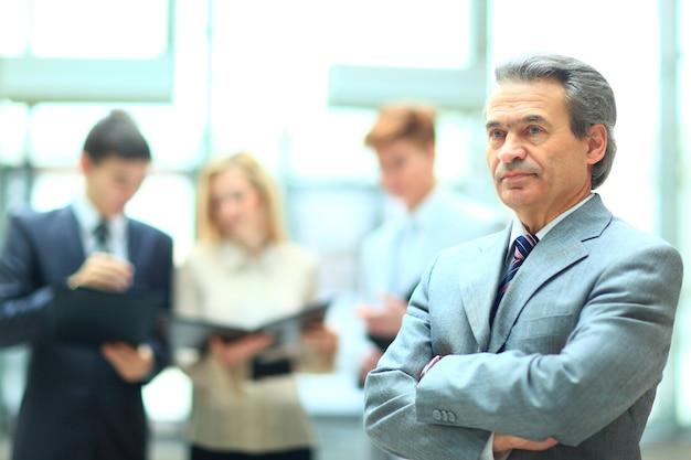 Szczęśliwy inteligentny biznesmen z kolegami z drużyny dyskutujących w tle