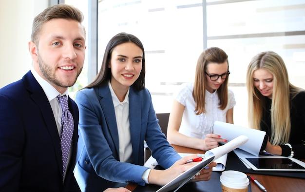 Szczęśliwy inteligentny biznesmen z kolegami z zespołu dyskutujących w tle