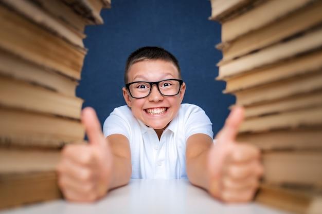 Szczęśliwy inteligentny chłopiec w okularach siedzi między dwoma stosami książek i patrzy na aparat uśmiechnięty, pokazując kciuk do góry.