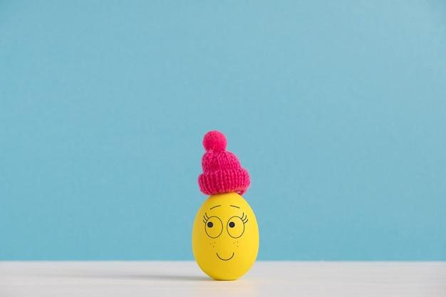 Szczęśliwy jajko w kapeluszu. koncepcja wakacji wielkanocnych z słodkie jajka z zabawnymi twarzami. różne emocje i uczucia.
