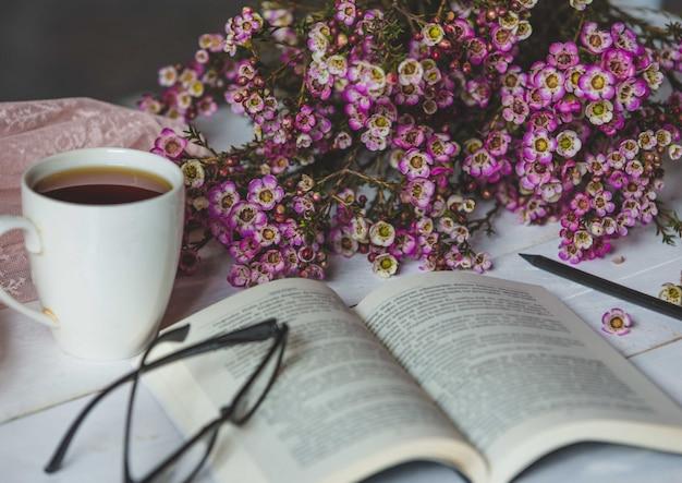 Szczęśliwy kącik, naturalne kwiaty, filiżanka herbaty, książka i szklanki