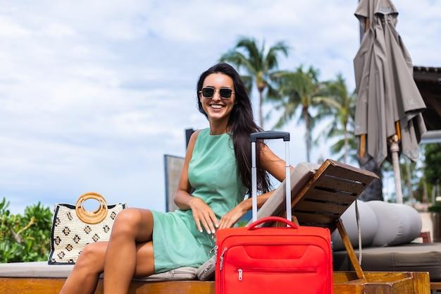 Szczęśliwy kaukaski bardzo długie włosy elegancka turystyczna kobieta w sukni z czerwoną walizką na zewnątrz hotelu