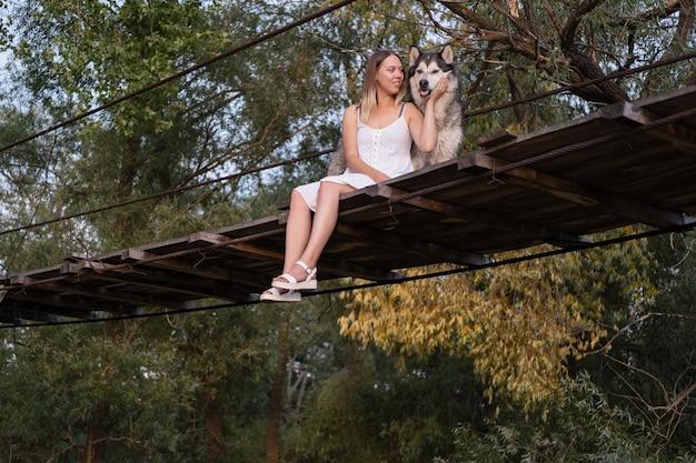 Szczęśliwy kaukaski blond kobieta w białej sukni obejmuje psa alaskan malamute na moście wiszącym. miłość i przyjaźń między człowiekiem a zwierzęciem.
