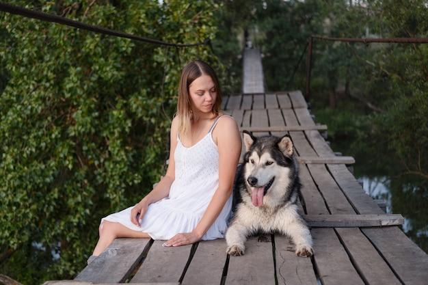 Szczęśliwy kaukaski blond kobieta w białej sukni pieścić alaskan malamute pies na moście wiszącym. miłość i przyjaźń między człowiekiem a zwierzęciem.