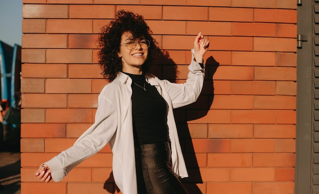 Szczęśliwy kaukaski dama z czarnymi kręconymi włosami nosi okulary pozuje na kamiennej ścianie na zewnątrz
