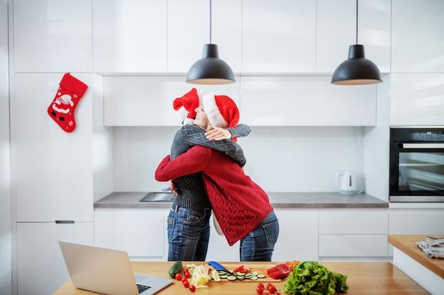 Szczęśliwy kaukaski kobieta starszy przytulanie córkę w ciąży, stojąc w kuchni. obaj mają na głowach czapki mikołaja. córka trzyma kartę kredytową. na blacie kuchennym są warzywa i laptop.