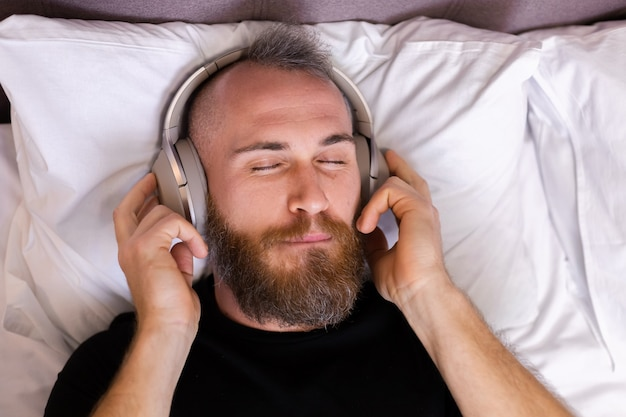 Szczęśliwy kaukaski mężczyzna na łóżku w słuchawkach słuchać ulubionej muzyki, odpoczywając samotnie, tańcząc.