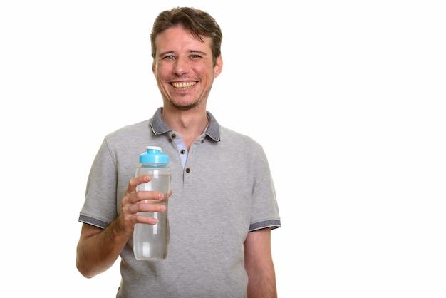 Szczęśliwy kaukaski mężczyzna trzyma butelkę wody podczas uśmiechu