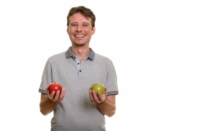 Szczęśliwy kaukaski mężczyzna trzyma czerwone i zielone jabłko