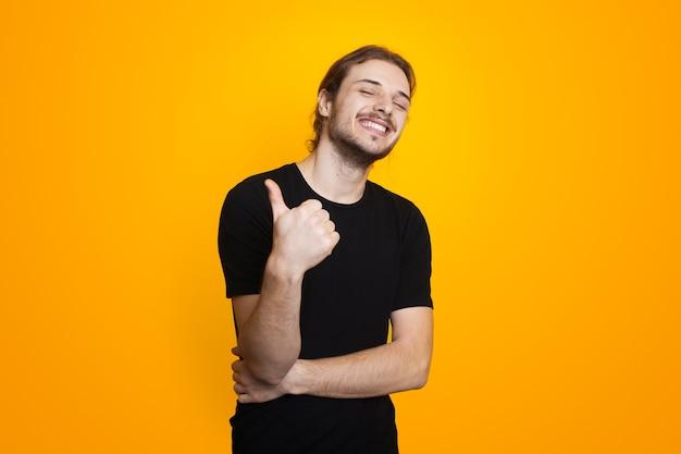 Szczęśliwy kaukaski mężczyzna z brodą i długimi włosami, wskazujący podobny znak i uśmiecha się w czarnych ubraniach na żółtej ścianie
