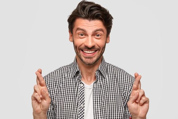 Szczęśliwy kaukaski mężczyzna z modną fryzurą, gestykuluje w pomieszczeniu, unosi skrzyżowane palce, wierzy w szczęście, szczerze się uśmiecha, nosi modną koszulę w kratę, odizolowaną od białej ściany. oczekiwanie