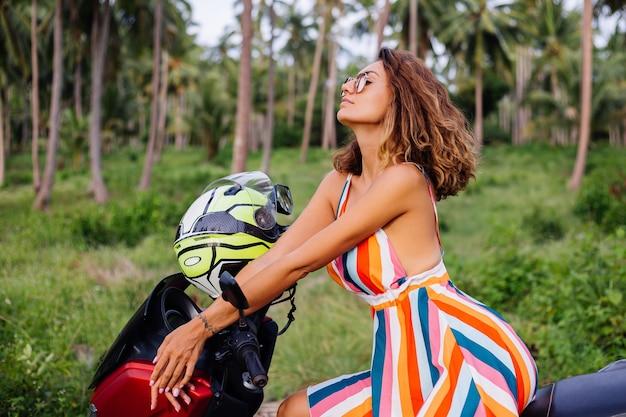 Szczęśliwy kaukaski rowerzysta kobieta w kolorowej letniej sukience na wakacje z kaskiem motocyklowym