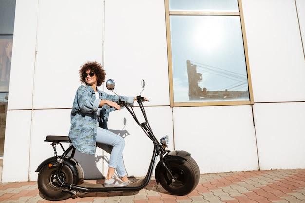 Szczęśliwy kędzierzawy kobiety obsiadanie na nowożytnym motocyklu