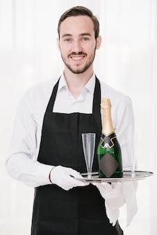 Szczęśliwy kelner gospodarstwa taca z szampanem