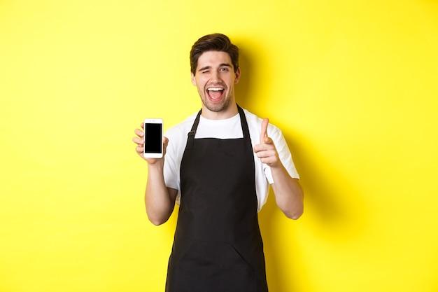 Szczęśliwy kelner pokazujący ekran telefonu komórkowego i kciuk w górę, polecający aplikację kawiarni-restauracji, stojący na żółtym tle.