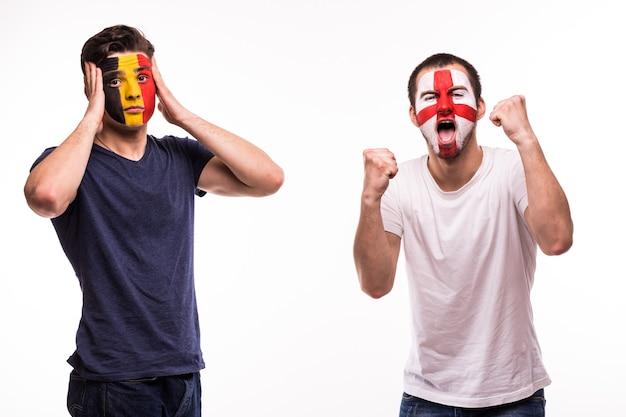 Szczęśliwy kibic anglii świętuje zwycięstwo nad zdenerwowanym kibicem belgii z pomalowaną twarzą na białym tle