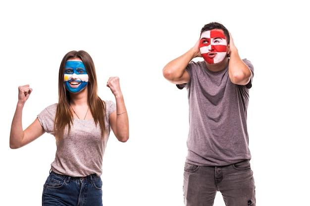 Szczęśliwy kibic argentyny świętuje zwycięstwo nad zdenerwowanym kibicem chorwacji z pomalowaną twarzą