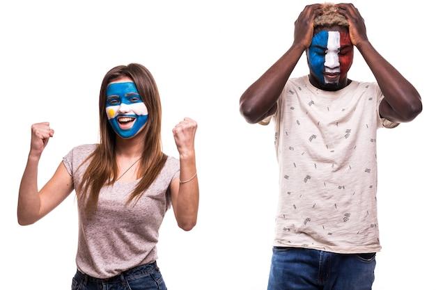 Szczęśliwy kibic argentyny świętuje zwycięstwo nad zdenerwowanym kibicem francji z pomalowaną twarzą