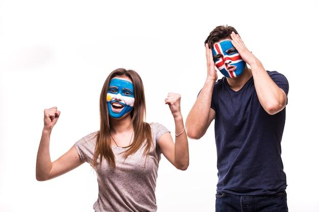 Szczęśliwy kibic argentyny świętuje zwycięstwo nad zdenerwowanym kibicem islandii z pomalowaną twarzą na białym tle